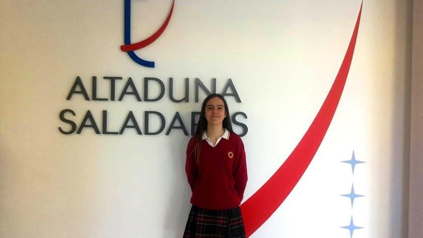 Mónica posa delante del logo de la institución.