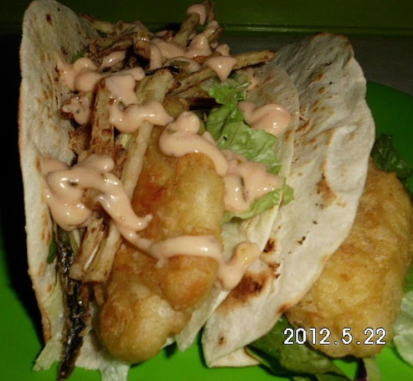 Place lettuce, fish and cucumber stings in flour tortilla.  Drizzle with tarter sauce...