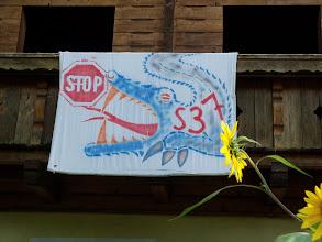 Photo: Ein Plakat, an einem der Häuser in Maria Saal. Im bergigen Österreich, durch die in den Tälern gelegenen Ortschaften, wo die Straßen manchmal sehr eng sind, fahren oft zu schnell große Lastkraftwagen. Das Missfallen der Einwohner weckt Proteste und wird oft in den Aufschriften an den Wegen widerspiegelt.