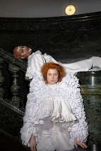 Photograph of me with short pink hair, wearing white lace facial decals, ornate ruffled and ruched white dress. I am reclining on a marble balustrade, and a similarly dressed pale skinned, ginger haired model is standing in front of me.