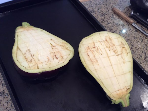 Heat oven to 360 degrees F. Cut aubergines in half lengthwise and slash flesh...