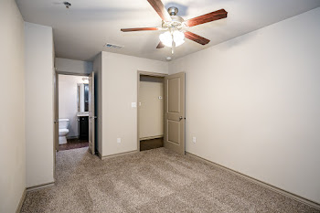 Greenwich bedroom with neutral carpet and ceiling fan