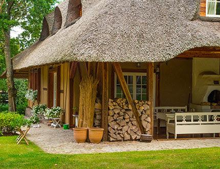 Elegancki domek pokryty trzciną wśród zielonych drzew
