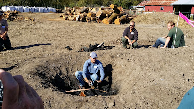 "Photo: Josiah Hunt describes the ""donut hole"" he leaves in the center of the pit kiln to help with firing."