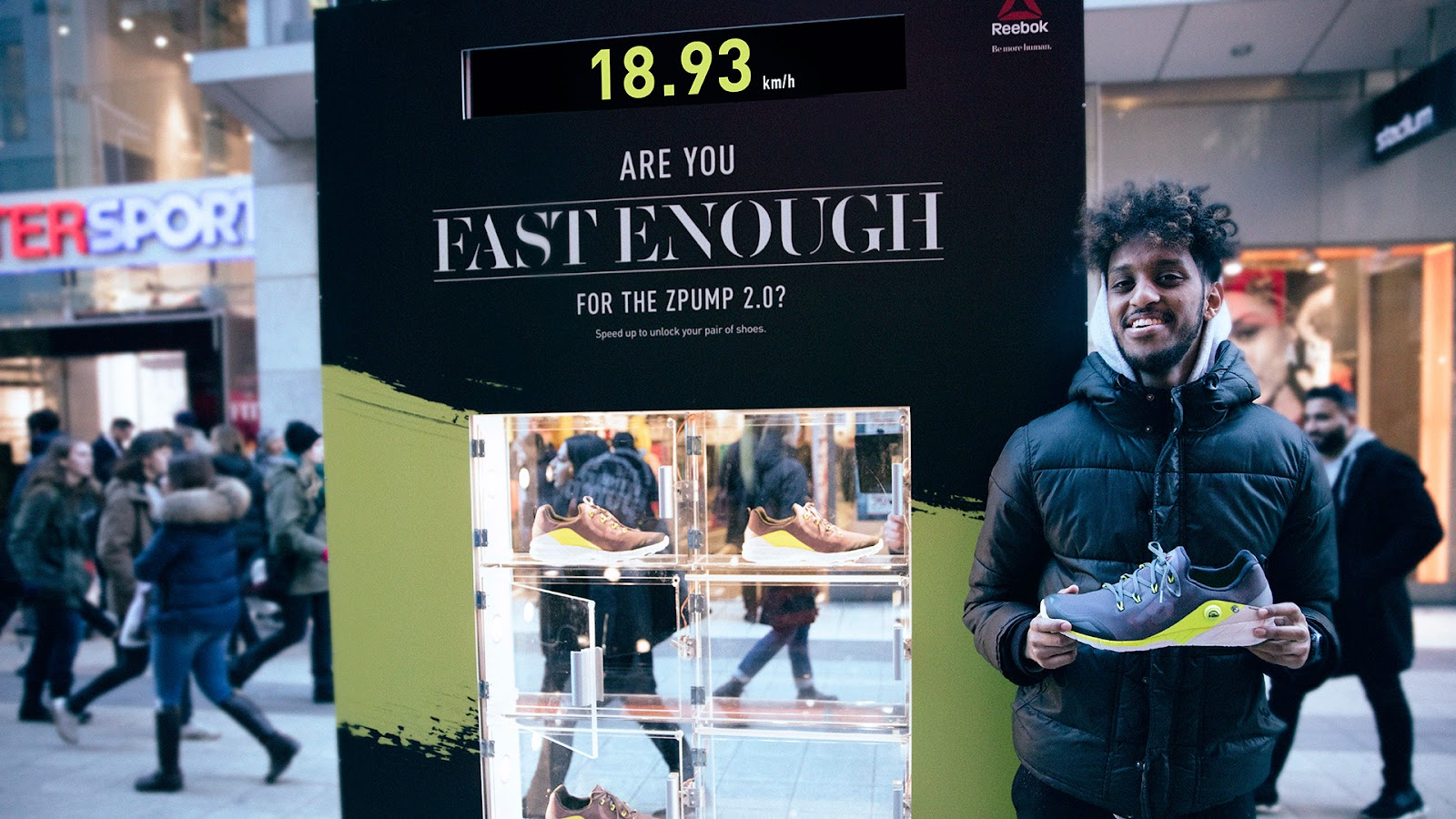 """Reebok's campaign, """"Are you fast enough for the ZPump 2.0?"""", a man standing next to the sign with his brand new trainers"""