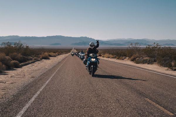 Grupo de motociclistas em uma estrada aberta.