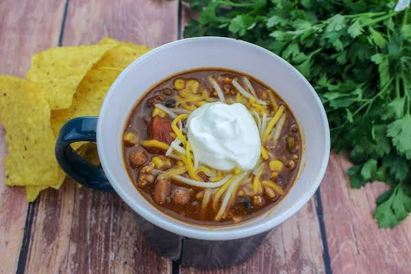 A Mug Of Krissy's Taco Chili Supreme With Shredded Cheese And Sour Cream.