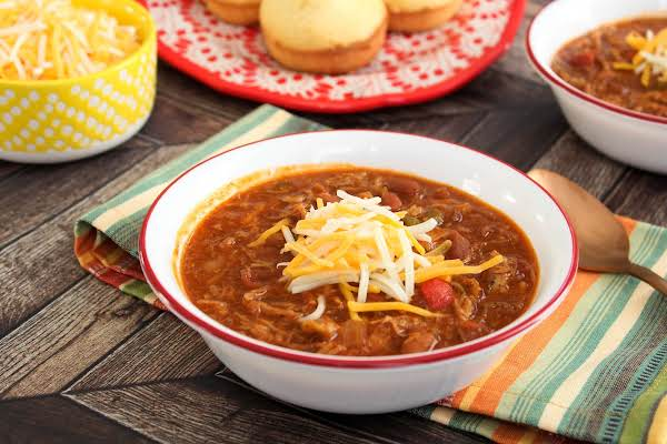 A Bowl Of Smoky Sweet Baby Back Chili With Shredded Cheese On Top.