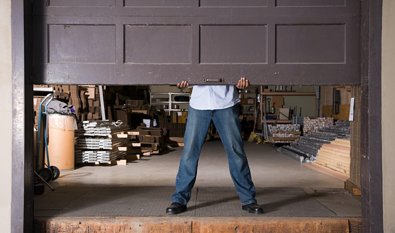 A man manually lifts open a garage door.