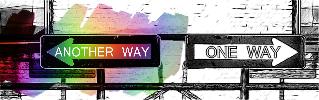 """A Black and white """"One Way"""" Arrow sign faces right, while a similar sign points left but is colored over in a rainbow and reads """"Another Way."""""""