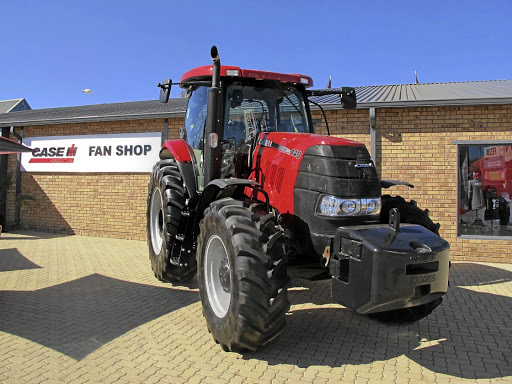 A Case IH tractor outside the essential merchandise shop.