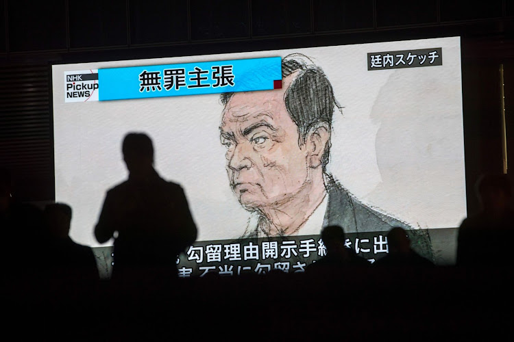 Pedestrians pass by a TV screen showing a news programme displaying a sketch of former Nissan chief Carlos Ghosn in the courtroom in Tokyo, Japan, on January 8 2019. Picture: AFP/BEHROUZ MEHRI