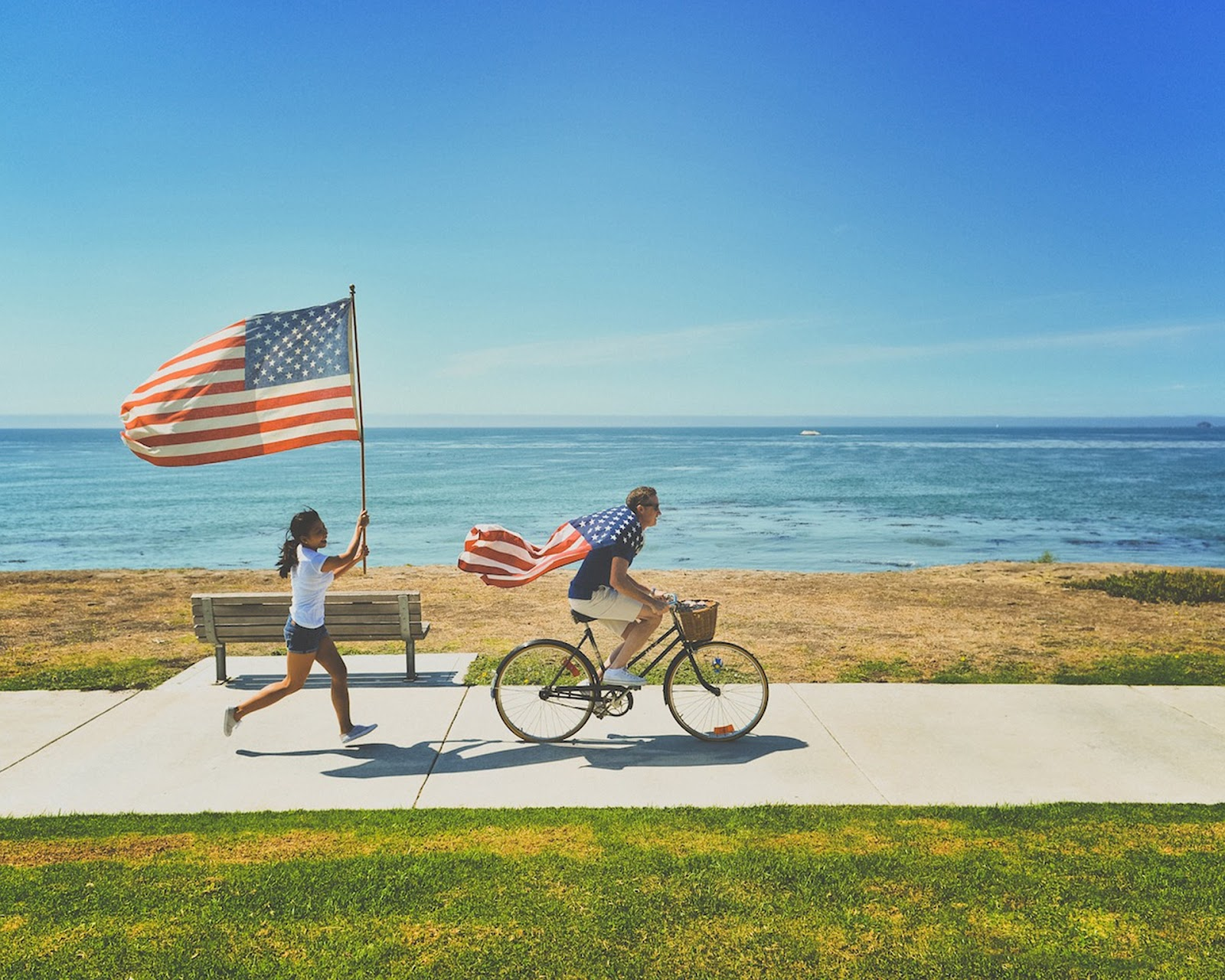 a boy riding his bike while using an American flag as a cape, and a girl running behind him while holding up another American flag