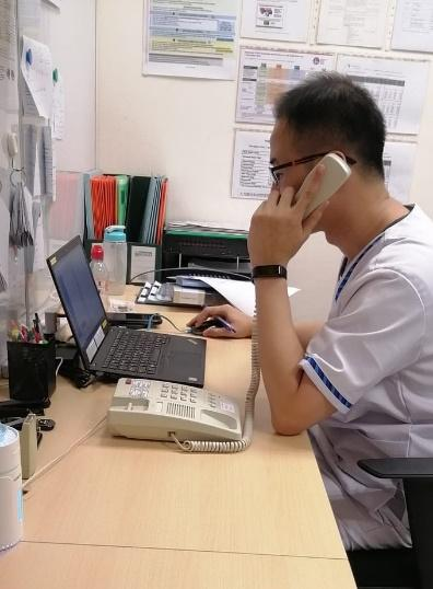 A person holding a phone to the ear and looking at a computer  Description automatically generated with low confidence