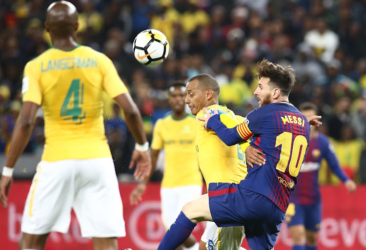Lionel Messi of FC Barcelona and Mamelodi Sundows captain Hlompo Kekana  fight for the ball during the Nelson Mandela Centenary Challenge at FNB  Stadium. a1158a4ad32