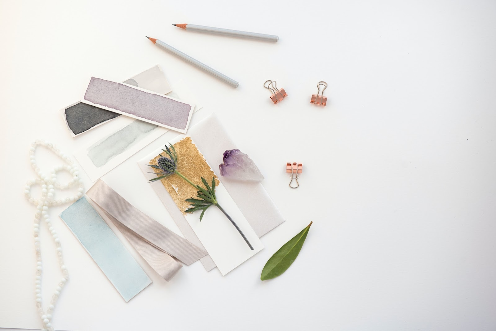 A selection of lilac and blue paint swatches, flowers, beads, and art materials are laid out on a plain white background.