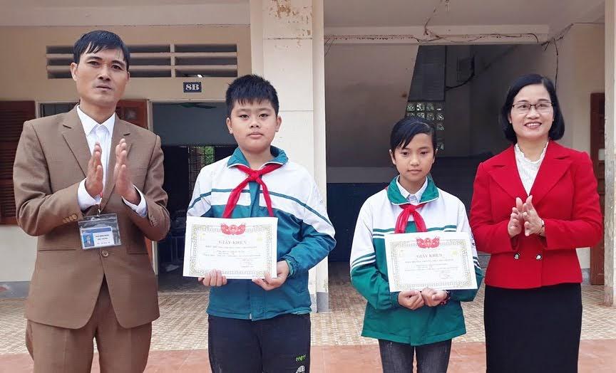 Ban Giám hiệu Trường THCS Thanh Lĩnh, huyện Thanh Chương tặng Giấy khen cho 2 em học sinh Nguyễn Thế Đan và Nguyễn Thị Hoài Linh