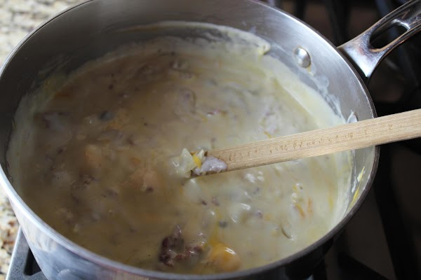 Add cheeses to cream sauce one handful at a time, stirring constantly and allowing...