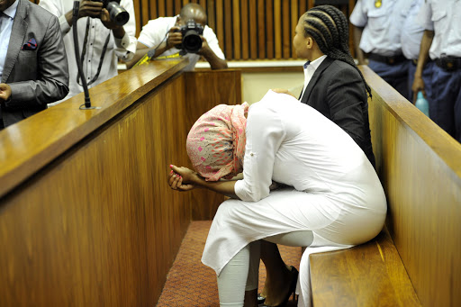 Sindisiwe Manqele covers her head with a scarf as she appears in the Randburg Magistrate's Court on December 9, 2015 in Johannesburg, South Africa. Manqele was found guilty of murdering her boyfriend, Nkululeko