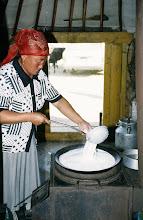 Photo: 03153 ブルド/ハスバータルイ家/乳製品作り/ウルムつくり/羊・山羊乳/小麦粉をひとつかみ入れながら杓子ですくっては鍋にかえす。泡立つ。