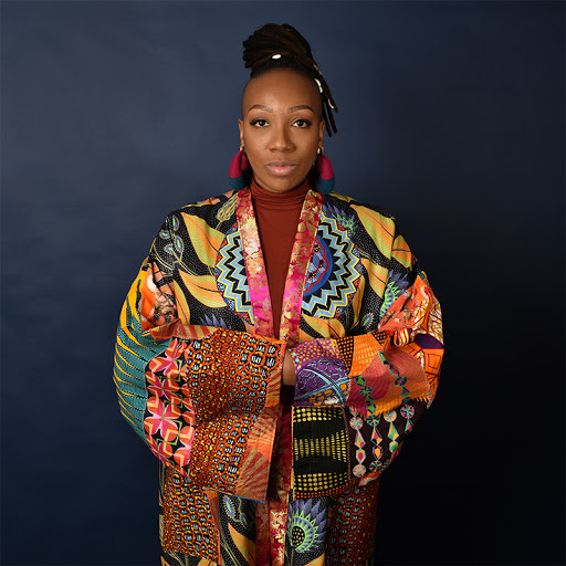 Portrait of artist with their arms crossed wearing a multi-colored kimono style jacket with geometric shapes in front of a black background.