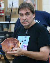 Photo: Tim Aley displays a cedar bowl with the bark inclusion.  He talked about another bowl from the same log that exploded with centrifugal force.