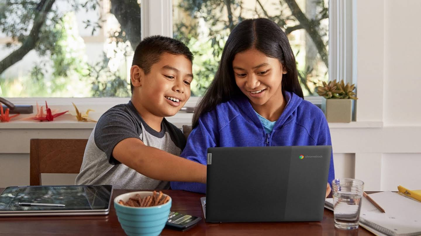 A young boy and girl work together at home in front of a Chromebook laptop.