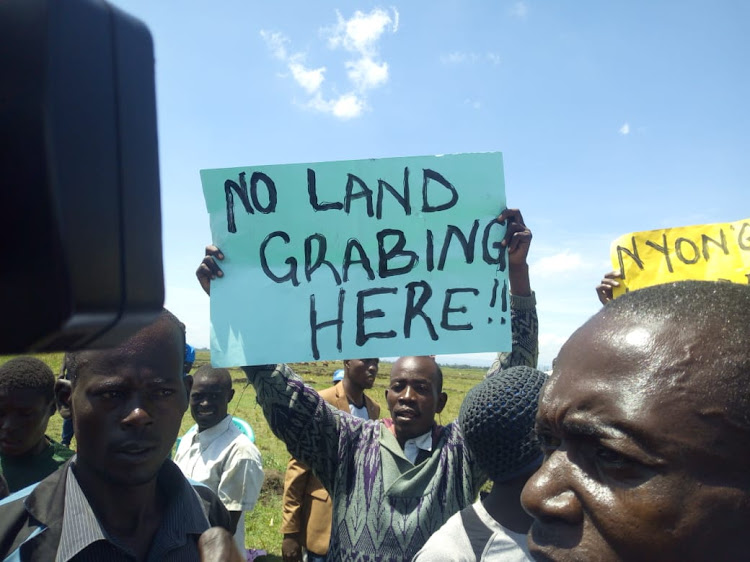 A resident of Ombeyi in Muhoroni carries a placard when they heckled ODM leader Raila Odinga on Monday May 13, 2019