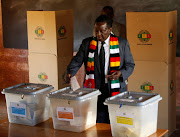 Zimbabwe's President Emmerson Mnangagwa casts his ballot as he votes in the general election at Sherwood Park Primary School in Kwekwe.