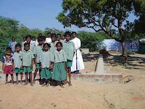 Photo: Class of children in front of the foundation for a new school.