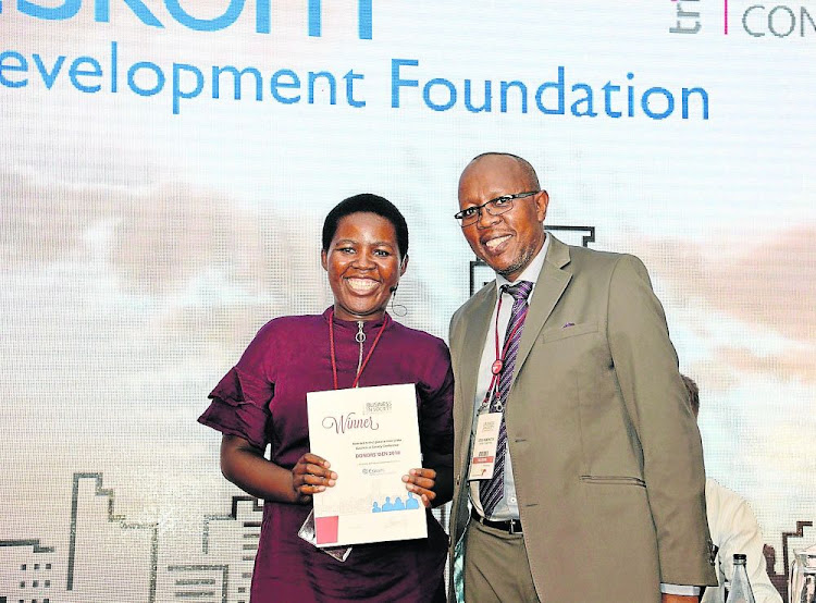 Eskom Development Foundation CEO Cecil Ramonotsi right congratulates Balisa Ntloko of Ikamva Youth