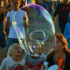 3 people and giant bubbles by Peter Murnieks - People Street & Candids ( events, street, block, children, beach, party, people, silly, friends, family, happy, pier, bliss, cheerful, groups, water, mothers, play, bubbles, kids, fun, blocks, fair, bubble, inside, air,  )