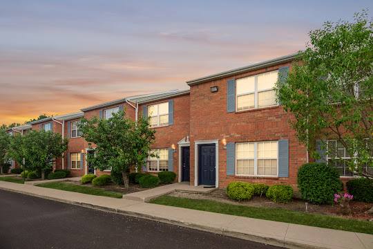 Timber Lake apartment building with red brick and light blue shutters at dusk