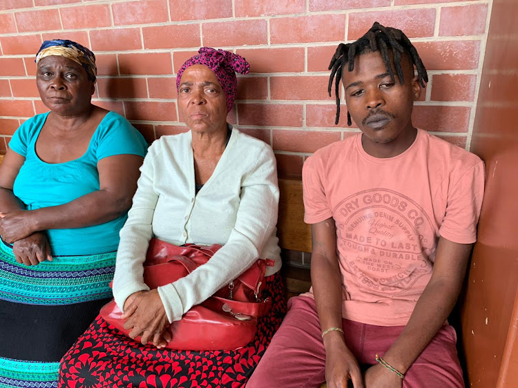 Julie Mathethidube and Ntombizanele Nodangala with Mxolisi Nodangala, the father of one-year-old Sibongakonke whose body was discovered in an open grassy area in Pheonix.