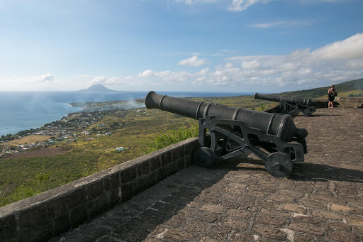 Brimstone-Hill-Fortress-cannons.jpg - Smoke from a cannon volley at Brimstone Hill Fortress? Nope. A brushfire below in Sandy Point Town, St. Kitts. The island of St. Eustatius looms in the distance.