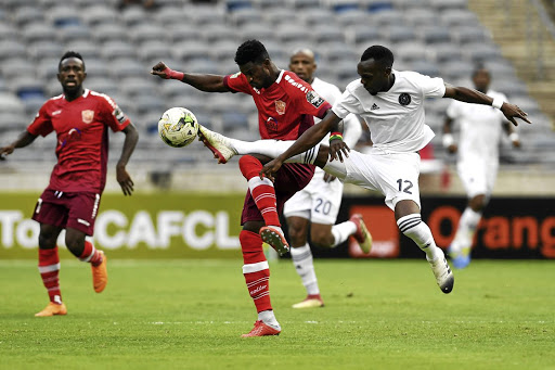 Horoya's Godfred Asante tries to block Justin Shonga of Pirates during their CAF Champions League tie on Friday.
