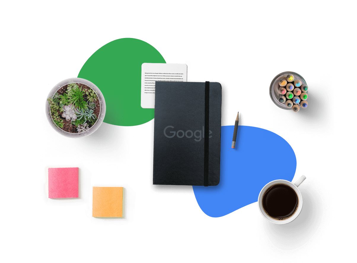 Google Notebook alongside a cup of coffee, a plant and a glass filled with crayons