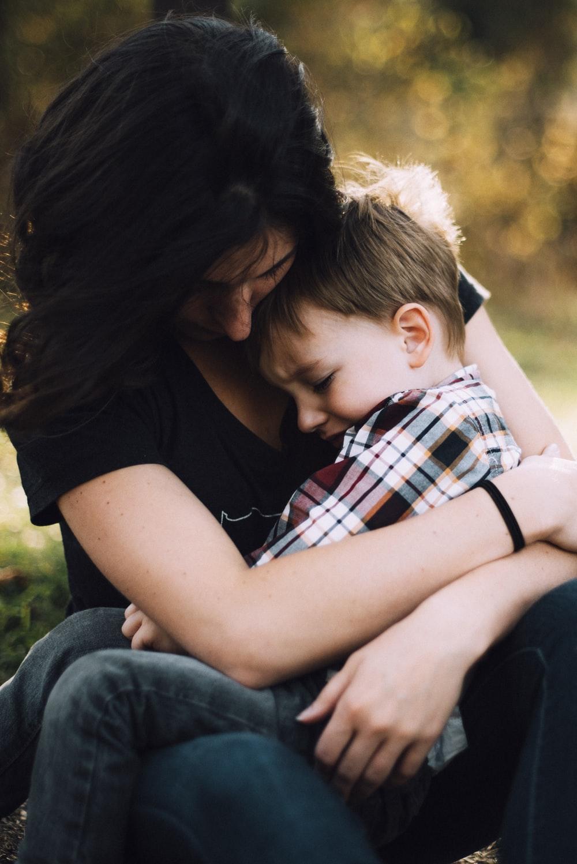 Description: woman hugging boy on her lap