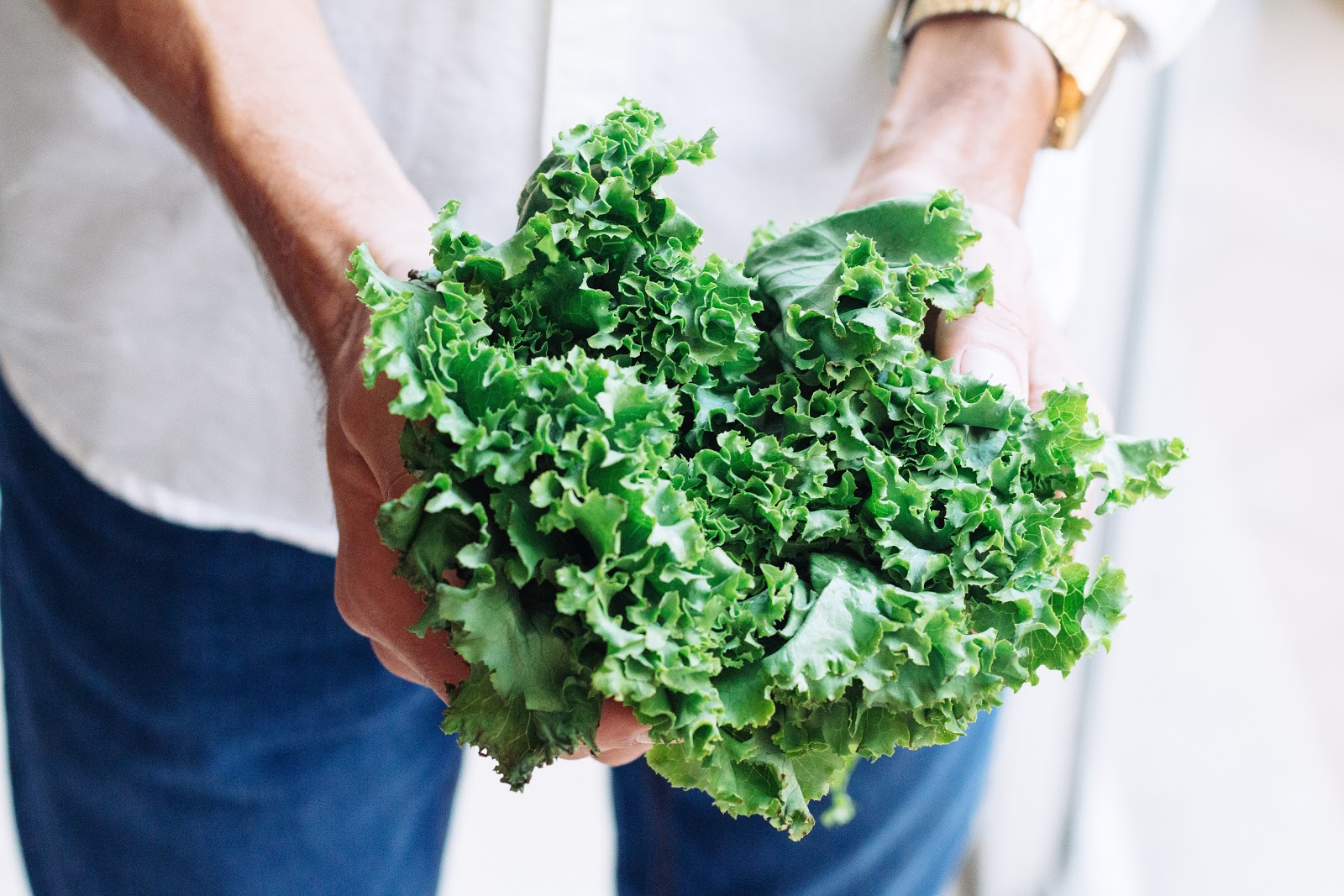 a woman holding one of the high-vibrations foods - kale