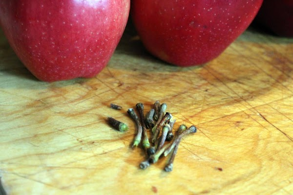 Stems removed from apples on a cutting board.