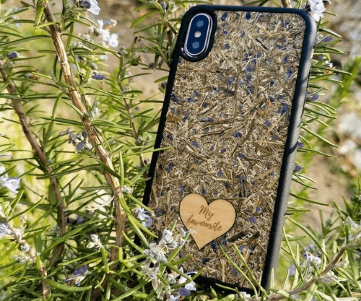 Sustainable iphone case made with real lavender flowers. Case is sitting outdoors in a Rosemary bush.