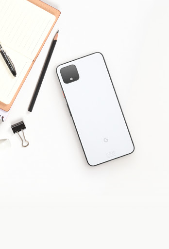 An overhead image of a Google Phone on a desktop next to a pencil, notepad, and binder clip.