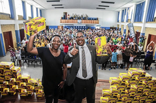 DJ Shimza and MEC Panyaza Lesufi happy about donation of school shoes.