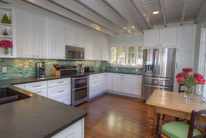 Photo: State of the art kitchen with beamed ceiling, stainless appliances, wood floors and stone countertops.