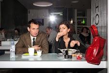 man en vrouw kijken op van een maaltijd; een grote rode damestas staat pregnant op de voorgrond