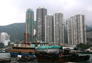 Photo: Vanhoja kalastajaveneitä ja uusia pilvenpiirtäjiä. Kanojen pito veneillä kiellettiin SARS-epidemian aikaan.