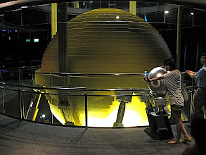 Photo: Side view of the ball showing four of the eight damping pistons and steel wrap-around supporting cables.  The largest reported amplitudes are 1.5 meters relative to the building.