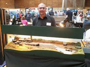 "Photo: 128 Chris Ford with the latest of a line of small 009 layouts he has built and exhibited over the years. ""Edge"" is rather different as it was not built for exhibiting purposes but as a ""work in progress"" project to illustrate a book on model railway construction that Chris has been writing. Now that Edge has been completed, he brought it along to ExpoNG and it was handed over to the safe custody of another 009 Modeller who lives in the West Midlands. Perhaps therefore, Edge will appear at another show sometime in the future? ."