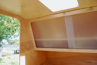 Photo: Interior cabinet over feet. This is our only storage for clothing, gear, etc. in the trailer so we made it angle out over our feet to get the most space. Doors were cut with a CNC machine (Austin's cousin helped us out with that!)