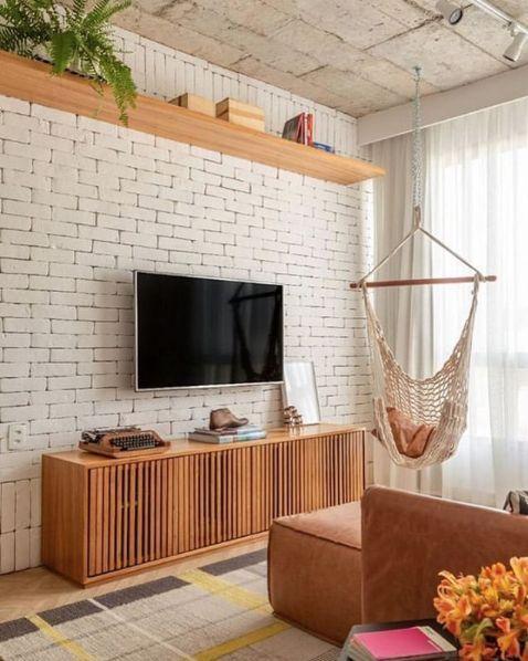 Sala com estilo rústico, tijolinhos branco na parede, rack e prateleiras de madeira, sofá marrom e cadeira de balanço.